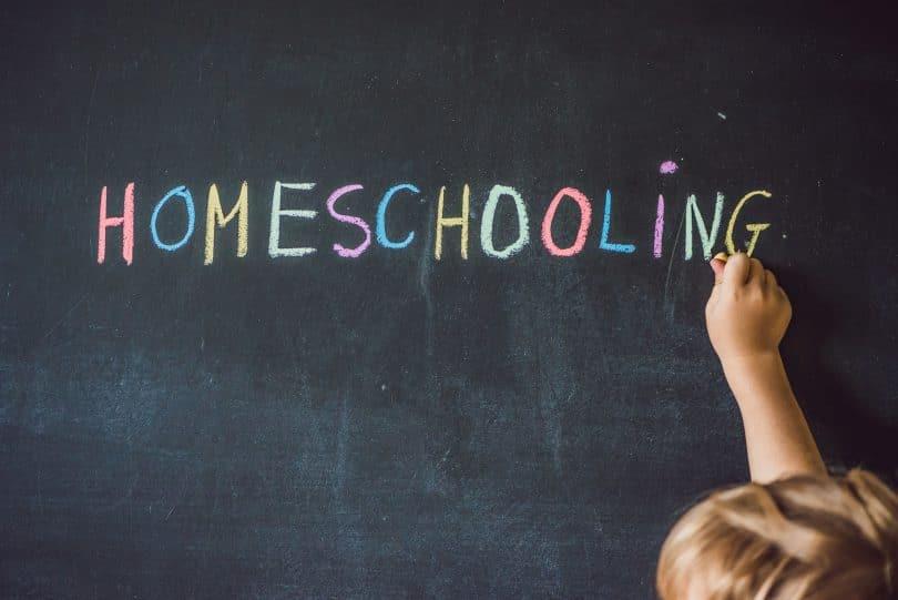 """Criança escrevendo em quadro negro com giz a palavra """"homeschooling"""" que significa Educação Domiciliar."""