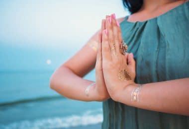 Mulher com as palmas das mãos juntas em frente ao peito.