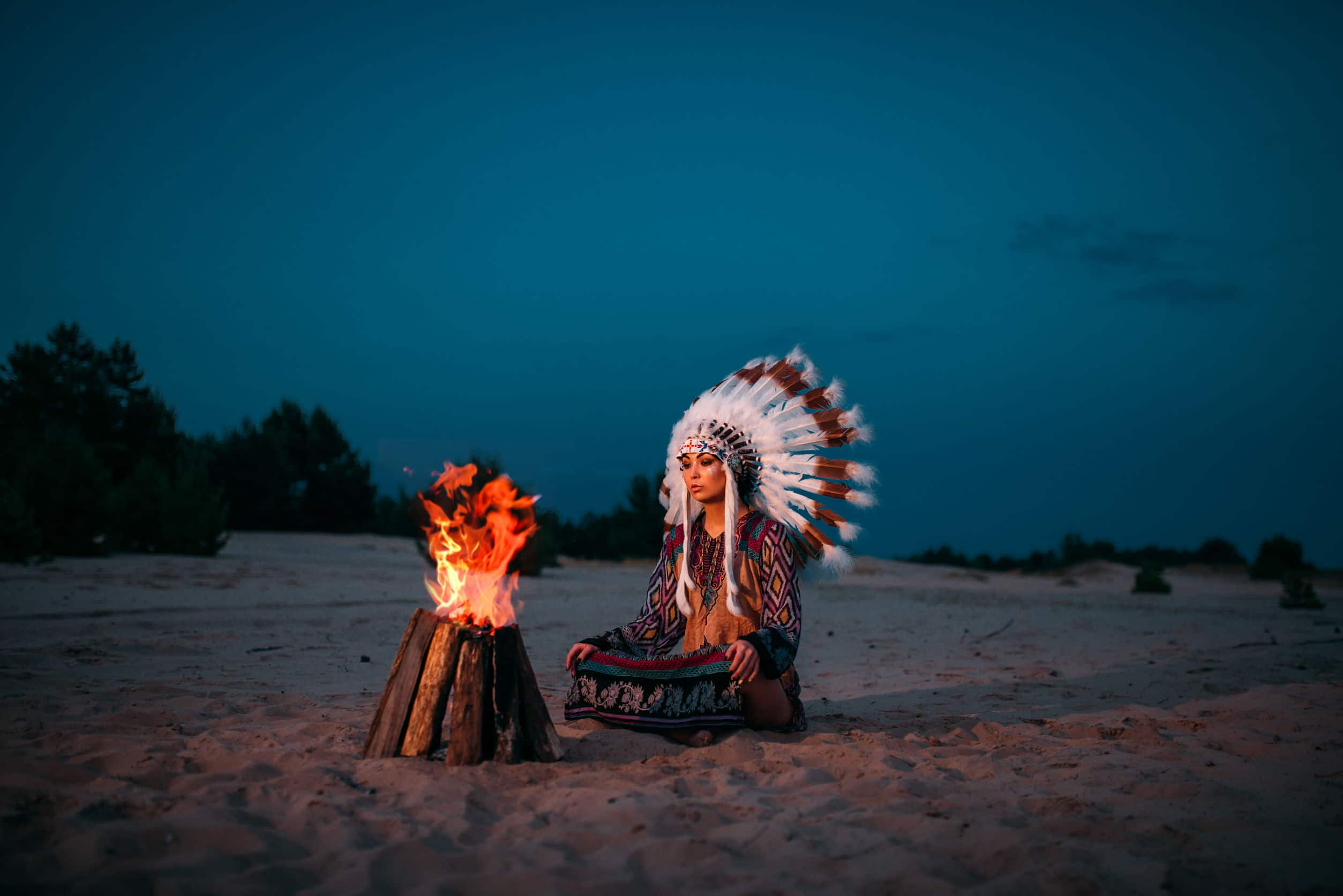 Índia americana em vestes de rituais sentada em frente de uma fogueira.
