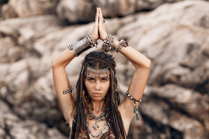 Foto de mulher morena vestida de índia com as mãos juntas em cima da cabeça.