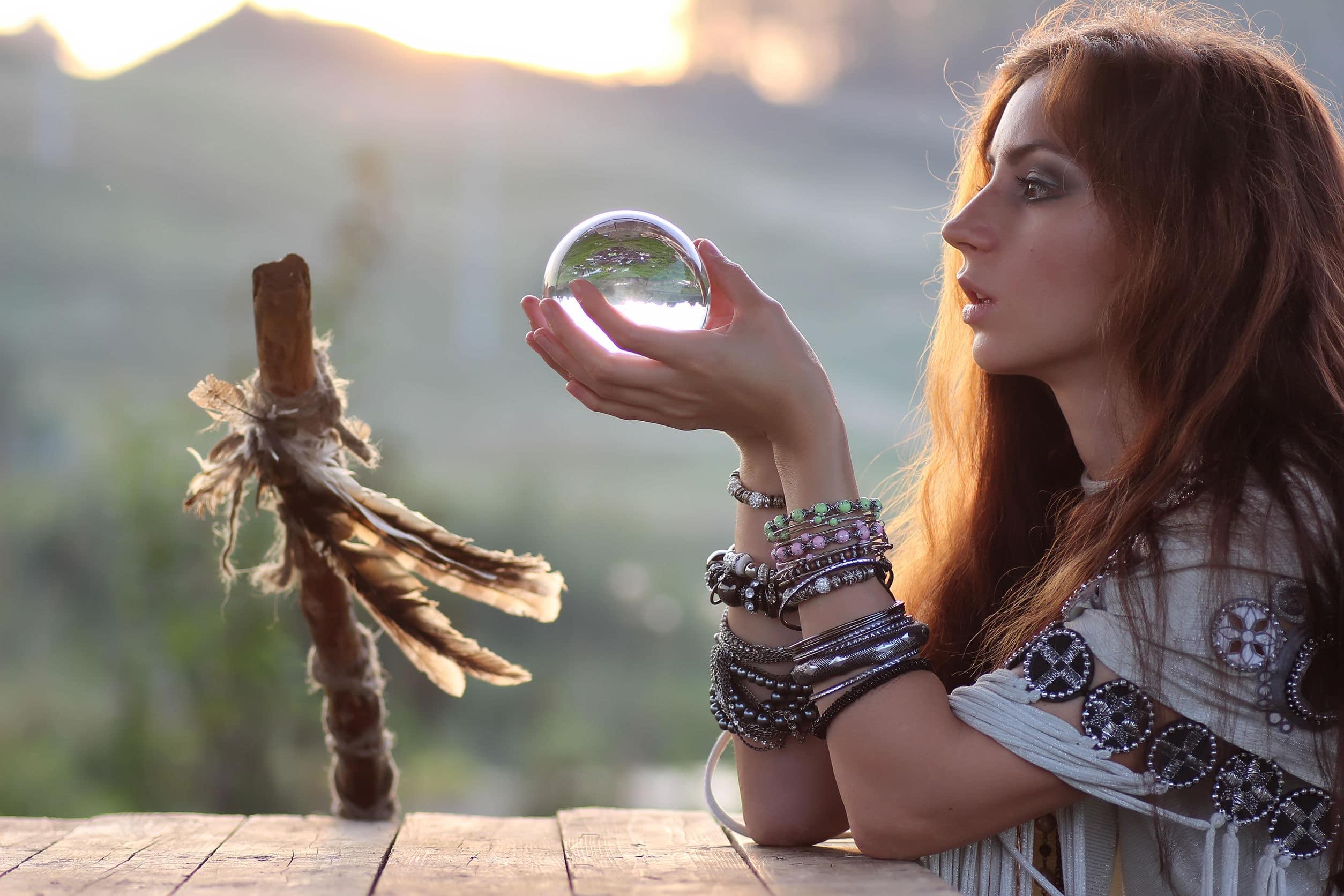 Mulher segurando uma esfera de cristal.