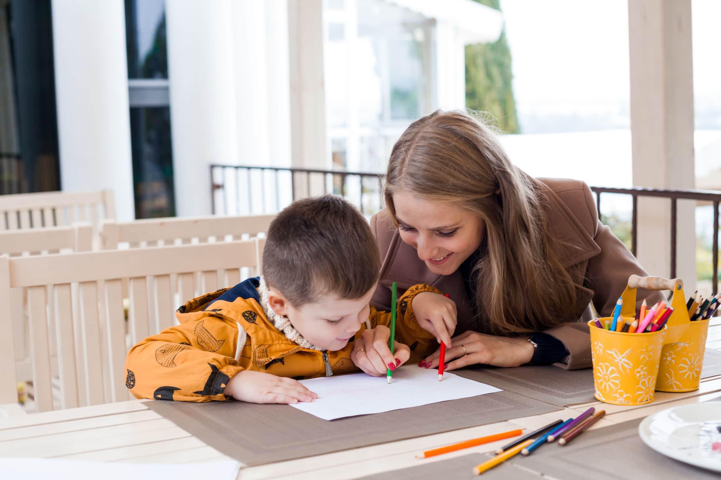 Filho e mãe fazendo lição juntos.