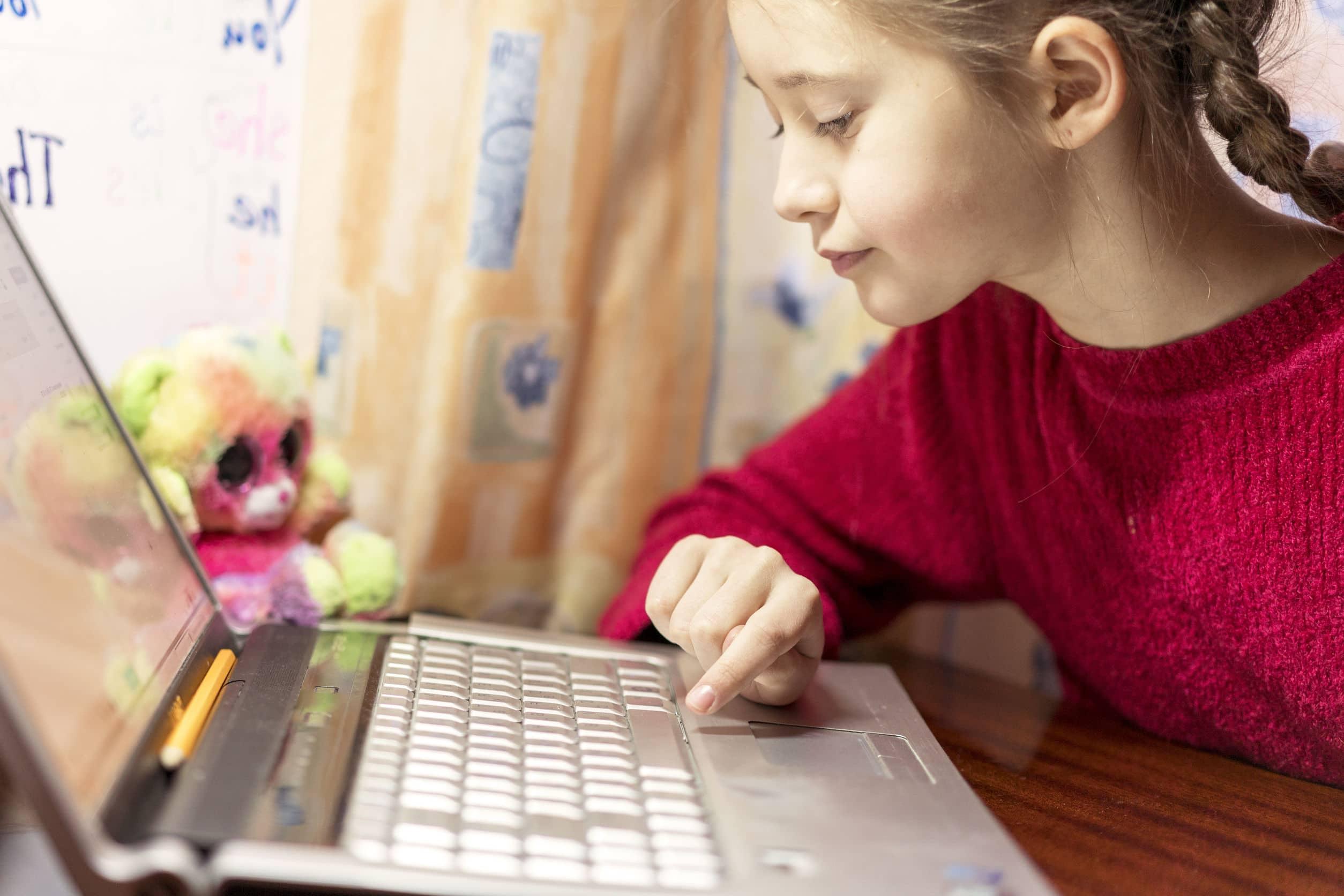 Menina usando blusa vermelha e trança no cabelo. Usando o computador no quarto. Ao lado um ursinho na cor verde e rosa.