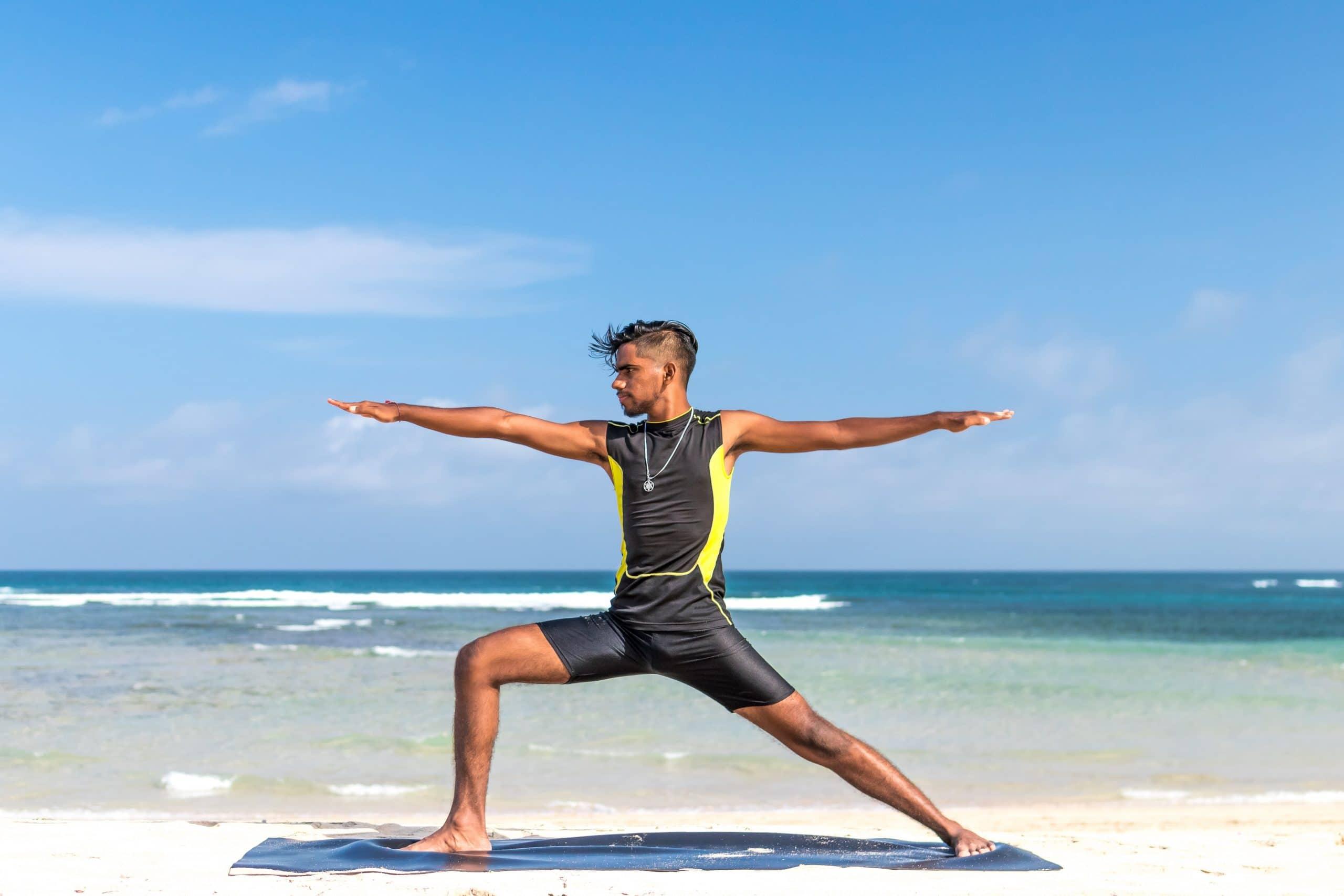 Surfista praticando Yoga na praia. Ele é moreno e usa roupa específica para surf.