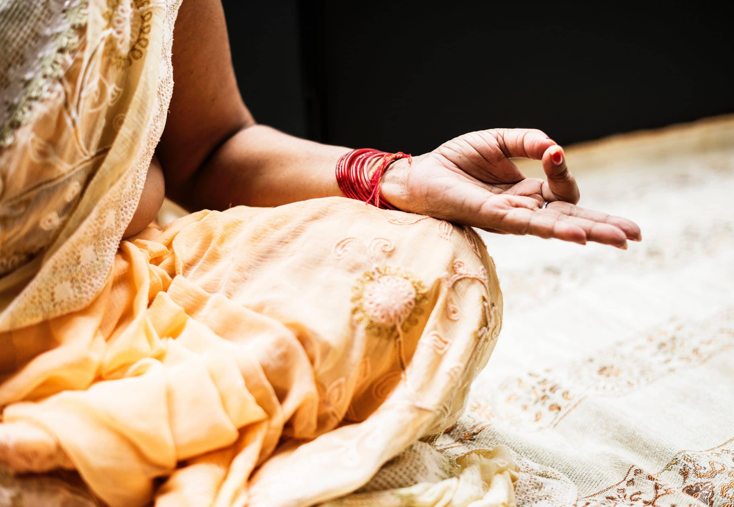 Mulher meditando. Aparentemente é indiano, ou está na Índia. Ela usa um vestido típico da região, nos tons laranja e amarelo. Usa uma pulseira vermelha.