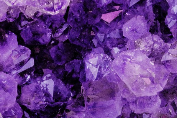 Pedra roxa com tons escuros e claros. Tem formato irregular, cheia de pontas.