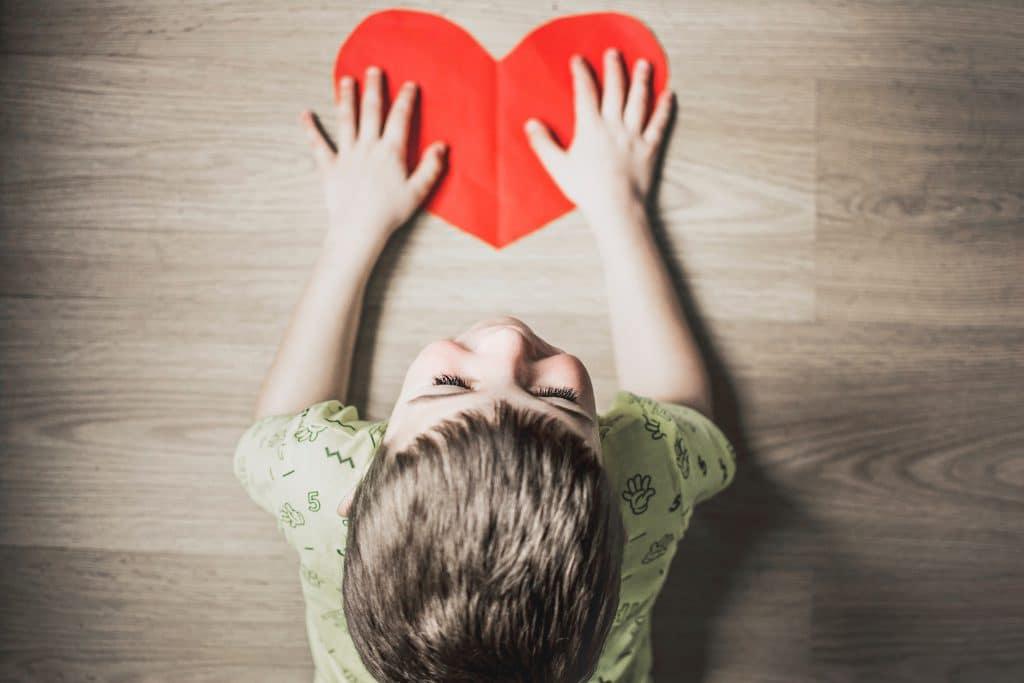 Criança deitada no chão com as mãos em cima de um coração feito de papel.