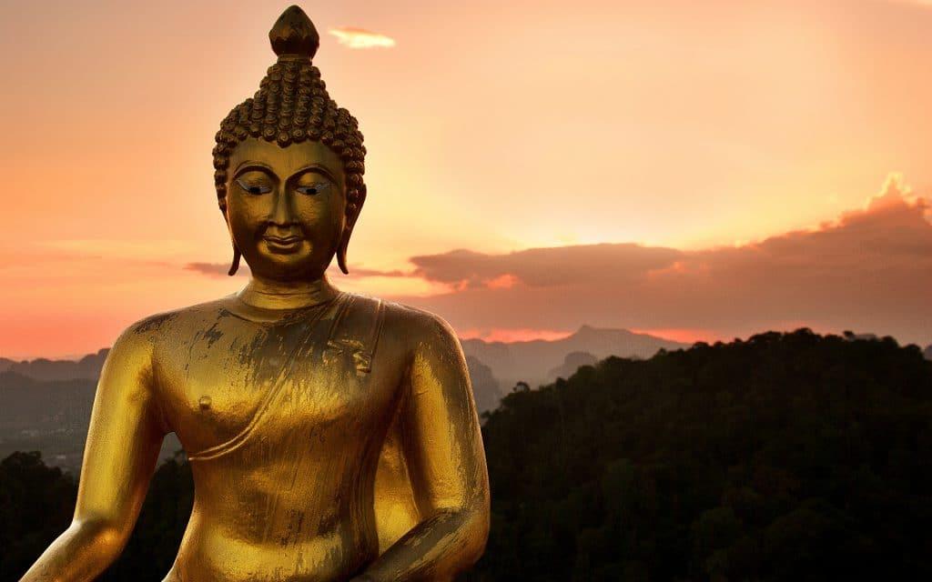 Estátua de Buda, ao fundo montanhas ao por do sol.