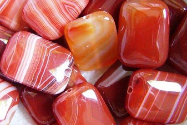 Pedra Cornalina. Laranja avermelhada com listras brancas.