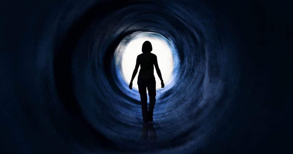 Silhueta de uma mulher contra aluz em túnel escuro.