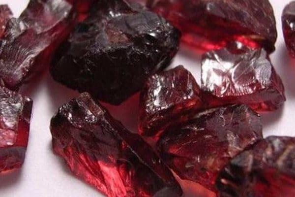 Pedra transparente na cor vermelha escuro. Em estado bruto e em diferentes tamanhos.
