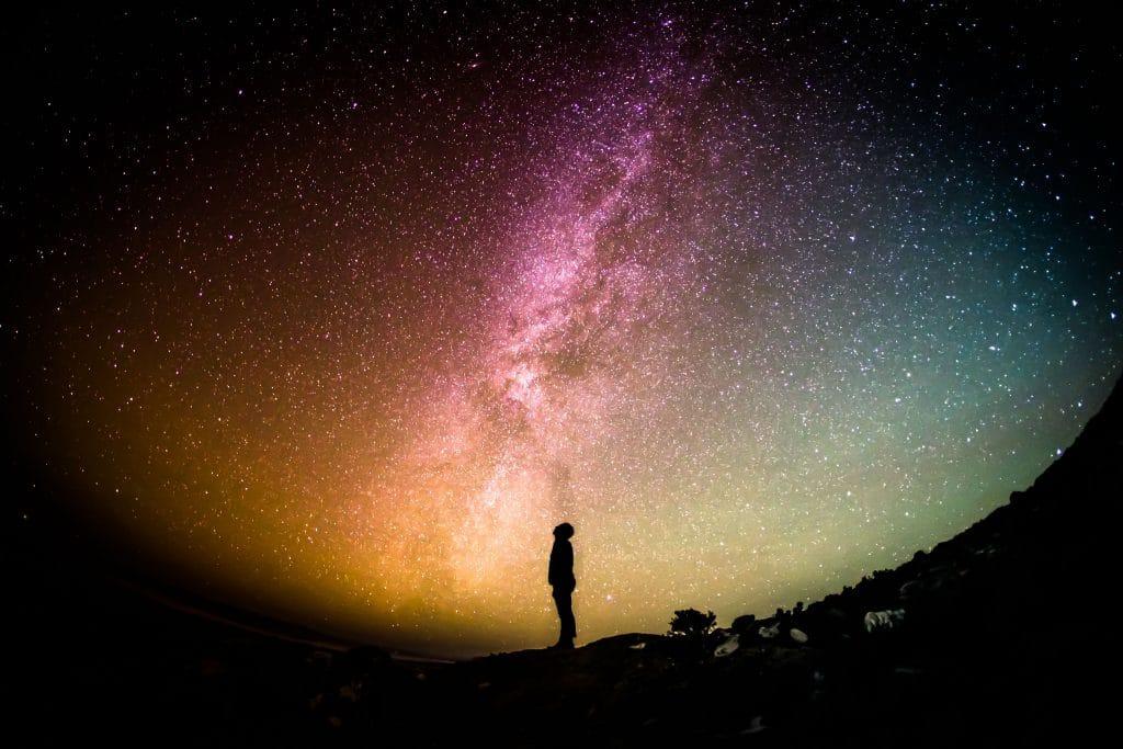 Silhueta de um homem olhando para cima e ao fundo há um céu estrelado.