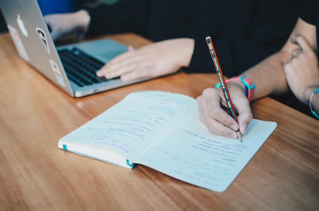 Duas pessoas sentadas apoiando um notebook e um caderno em uma mesa.