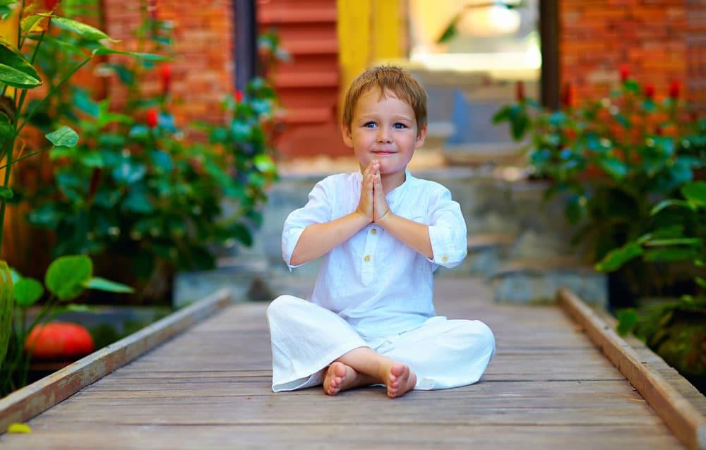 Menino de aproximadamente oito anos sentaod em posição meditativa com as pernas cruzadas e as mãos juntas sentado em chão d emadeira vestindo roupas brancas.