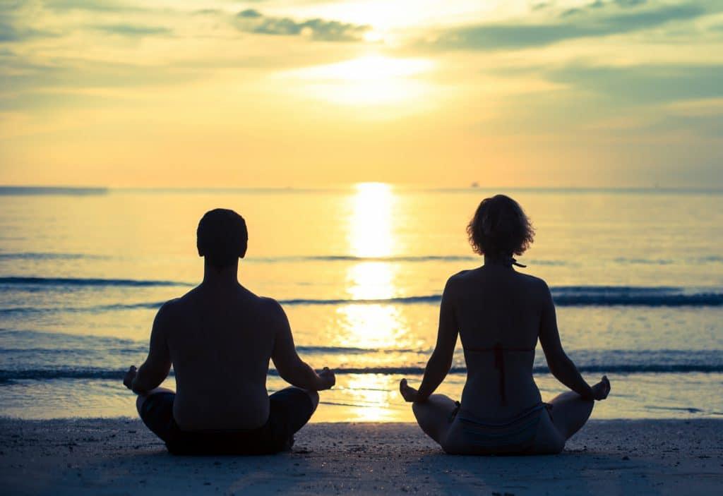 Duas pessoas sentadas de frente par ao mar meditam em posição de lotus.