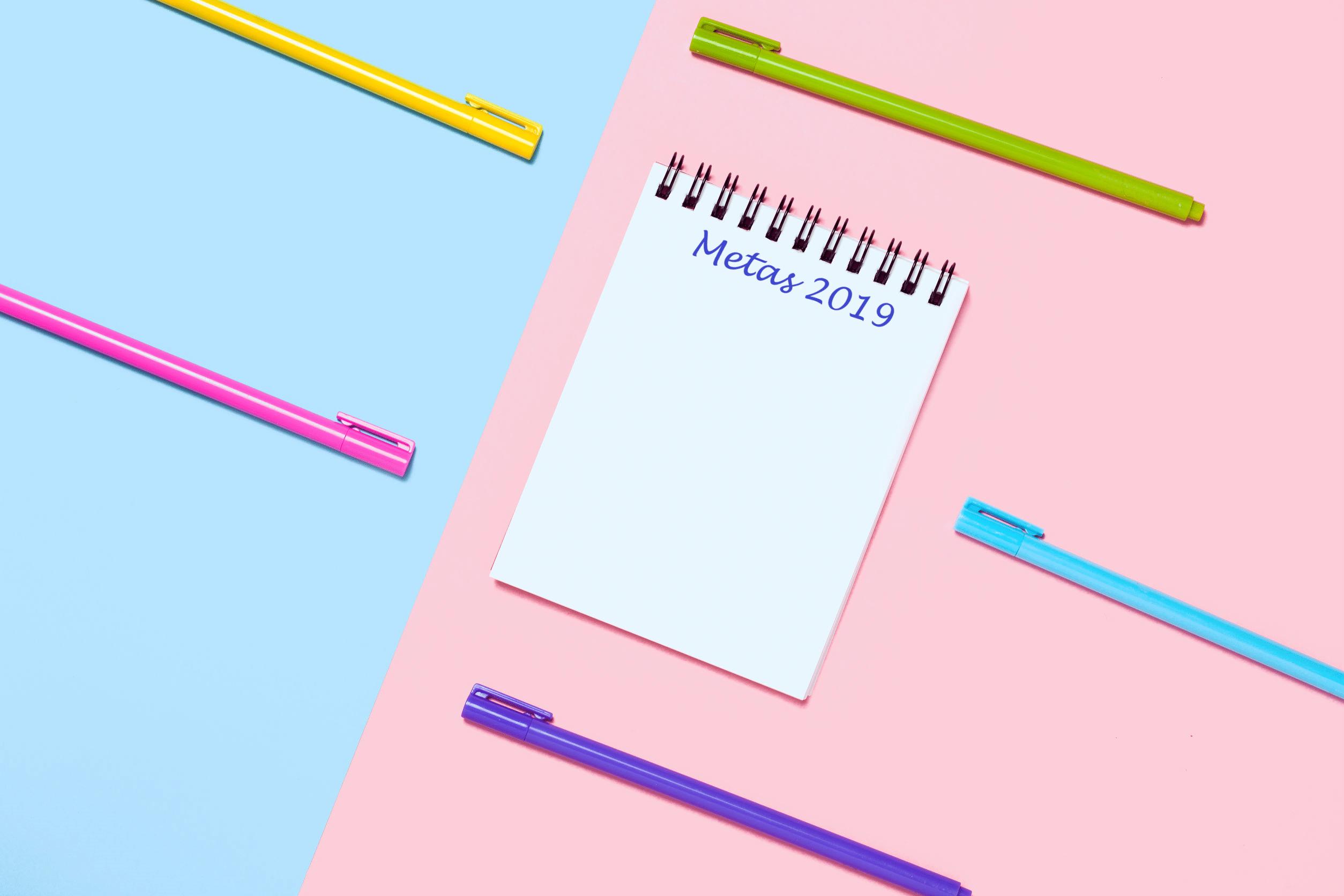Caderno com lista de metas para 2019. Mesa nas cores azul e rosa. Cinco canetas espalhadas na tela nas cores amarelo, verde, rosa, azul e roxo.