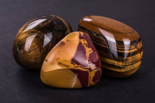 Pedra olho de tigre. Pedra na cor caramelo com manchas e listras na tonalidade marrom.