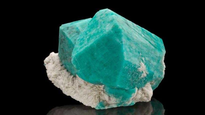 Amazonita. Pedra azul com parte branca embaixo.
