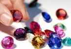 Mão segurando pedra preciosa vermelha. Ao lado outras pedras preciosas, todas de cores diferentes.