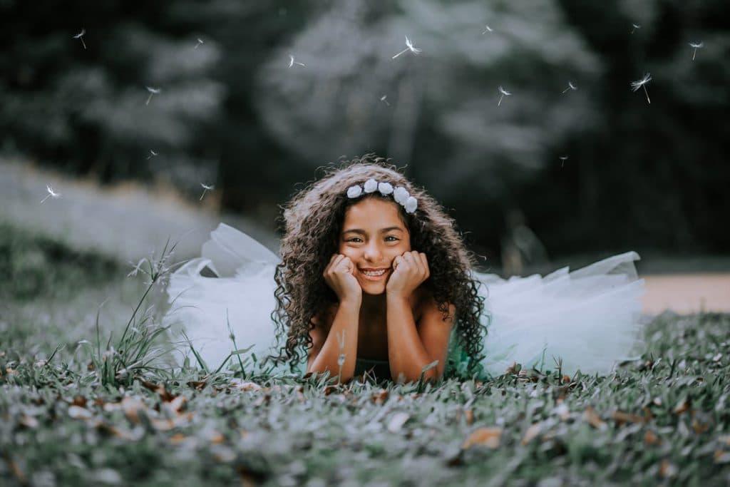 Menina de cabelos crespos deitada na grama sorrindo.