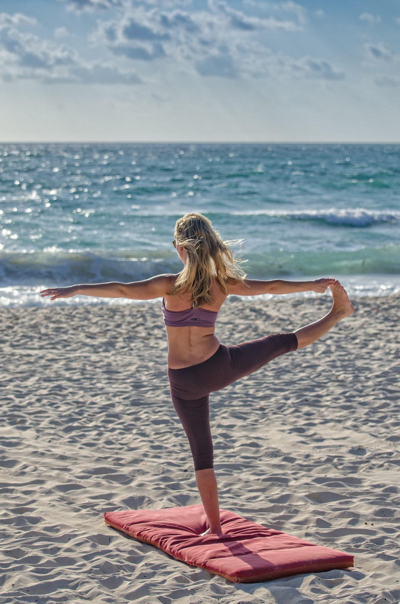 Mulher loira praticando Yoga na praia. Usa um top lilás e uma calça roxa. Usa também um tapete vermelho.