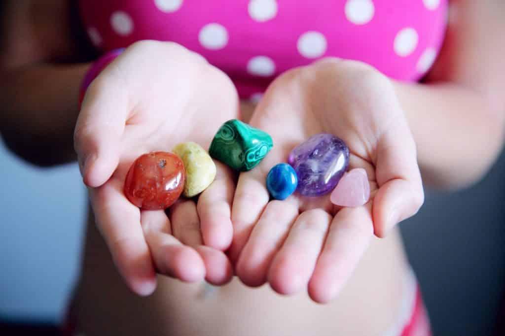 Menina de biquíni segurando nas mãos as pedras de chakras