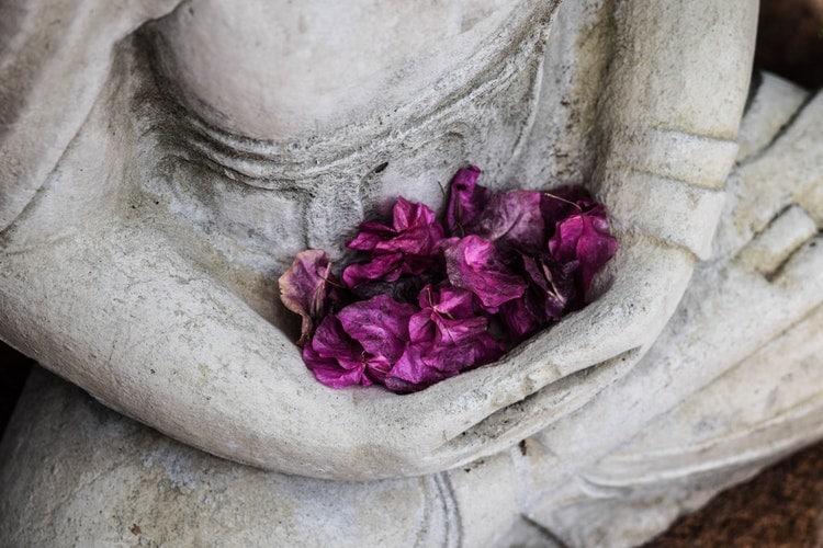 Estátua de uma pessoa com braços cruzados e há pétalas de flores roxas entre os braços da estátua.