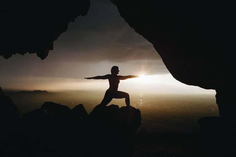 Silhueta de uma mulher em posição de Yoga em uma montanha.