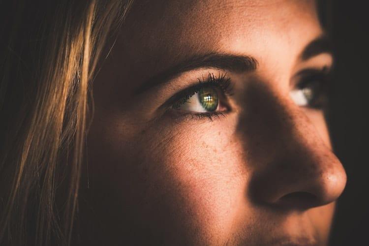 Olhos de uma moça loira olhando para o horizonte.