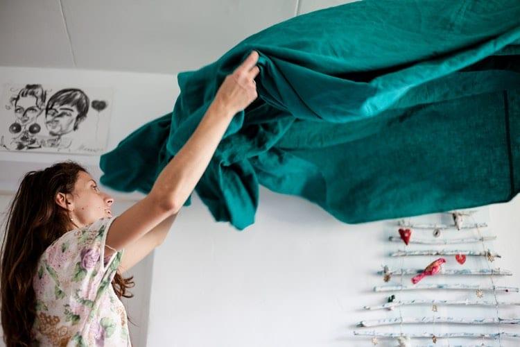 Mulher estendendo um lençol verde.
