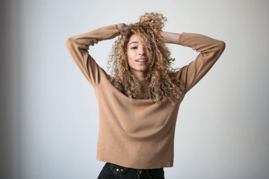 Menina com o cabelos loiros e crespos sorrindo com as mãos na cabeça.