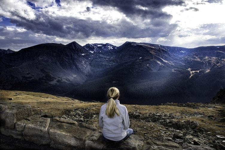 Mulher sentada em pose meditativa e ao fundo há uma paisagem de montanhas.