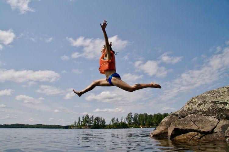 Mulher pulando em um lago.