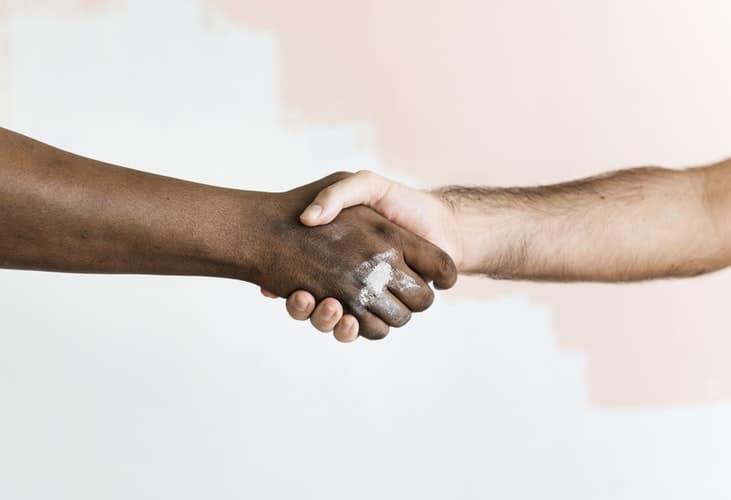 A imagem está fechada em duas mãos, de pessoas diferentes, que estão se apertando em sinal de ajuda.