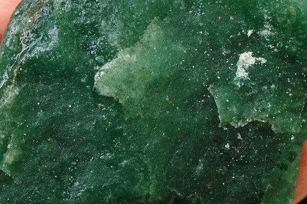 Pedra verde escuro. Fosca pois está em estado bruto.