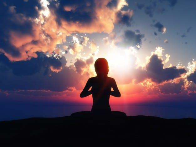 Silhueta de uma mulher em posição meditativa com fundo de nuvens ao anoitecer.