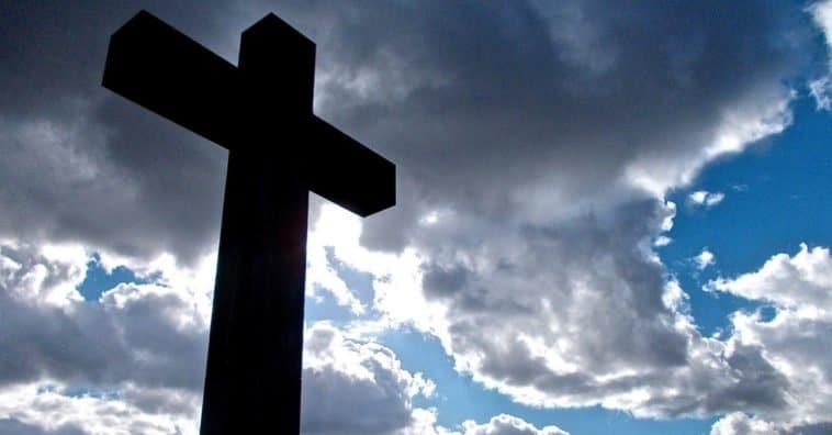 Uma cruz vista de cima para baixo sob o céu azul com nuvens.