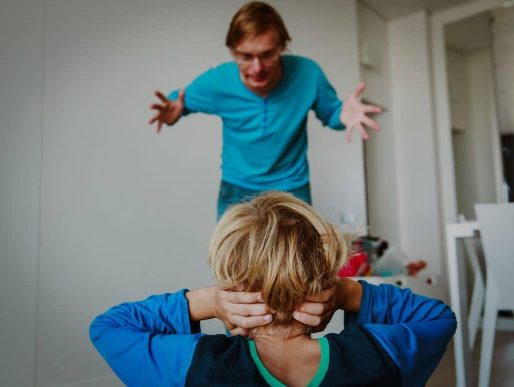 Homem branco, vestindo roupas azuis, em um quarto branco, gritando com menino que esta ajoelhado na sua frente, tentando tapar os ouvidos.