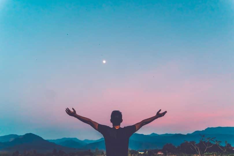Homem com as mãos levantadas para o céu.