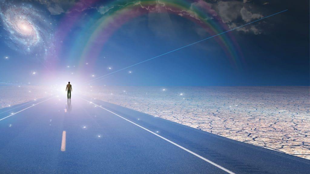 Ilustração gráfica de silhueta de pessoa andando em uma estrada em direção de uma luz brilhante no fim do horizonte. Ao fundo, no céu, há pintado um arco-íris e galáxias.