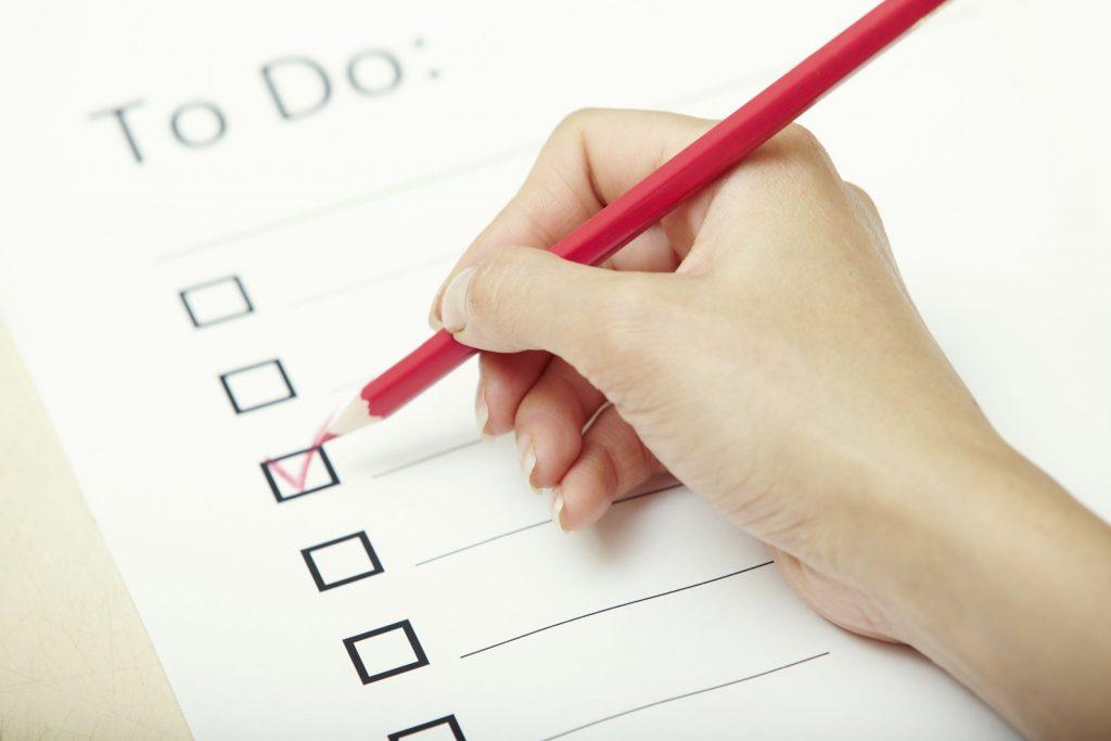 Mão de pessoas preenchendo com um lápis vermelho uma folha branca com uma lista de coisas para fazer.