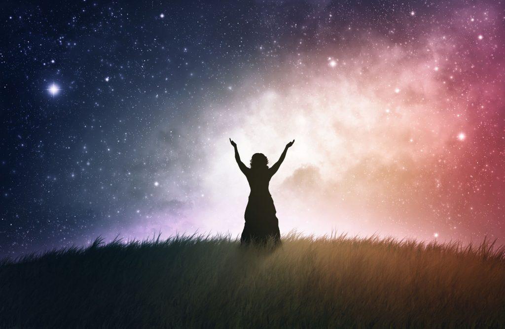 Silhueta de mulher em um campo, com os braços levantados, com o céu estrelado azul e rosa ao fundo.