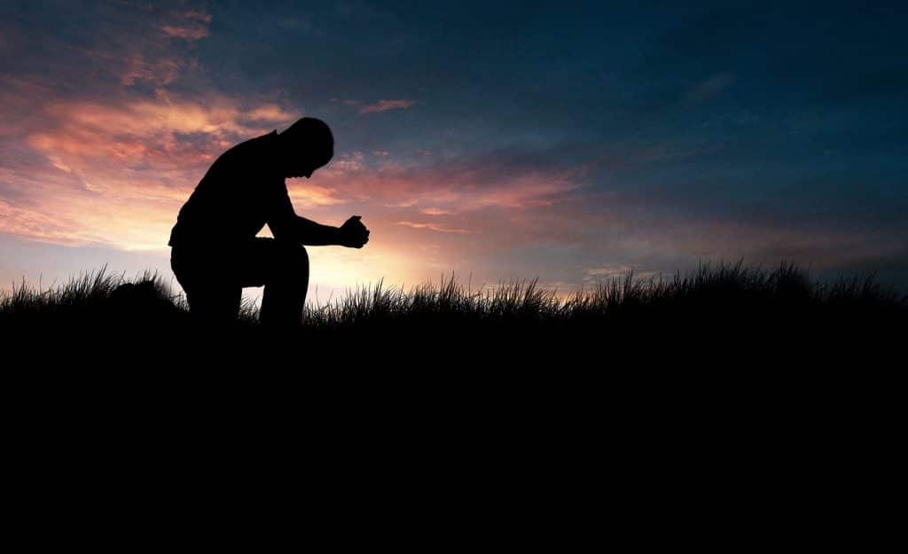 Homem ajoelhado na grama em posição de oração.