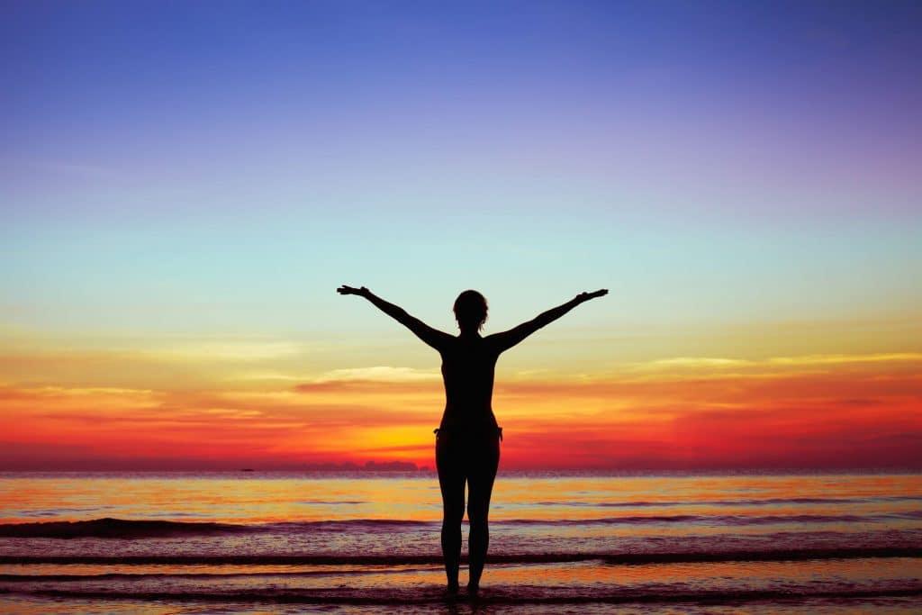Mulher com os braços estendidos para paisagem de mar. Fundo de pôr-do-sol.