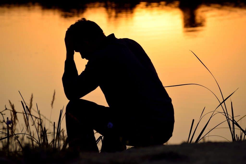 Silhueta de homem triste, cabisbaixo, ajoelhado na beira de um lago, com o pôr do sol ao fundo.