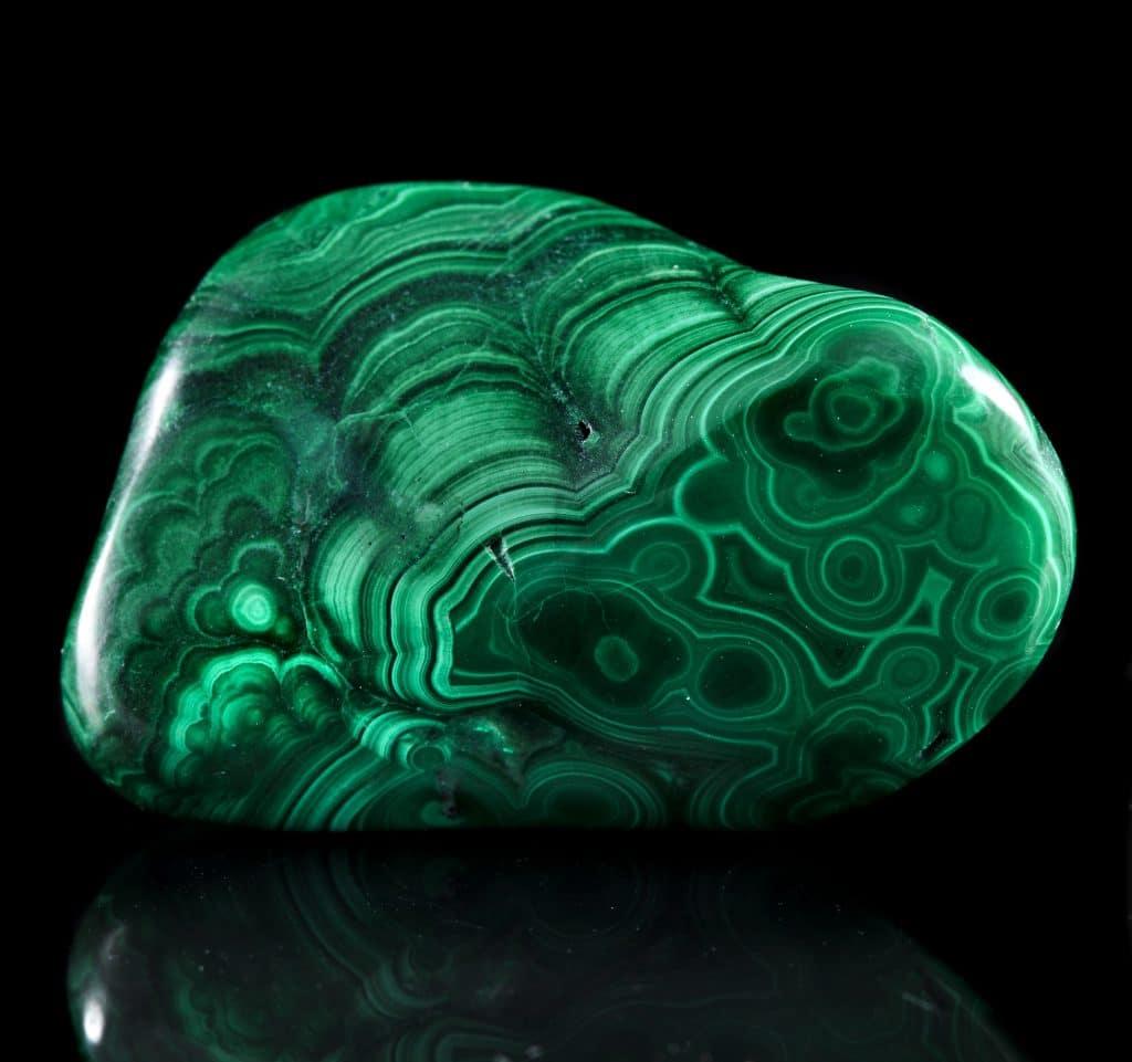Pedra malaquita. Pedra com tons de verde e preto. Contém um padrão de desenhos circulares.