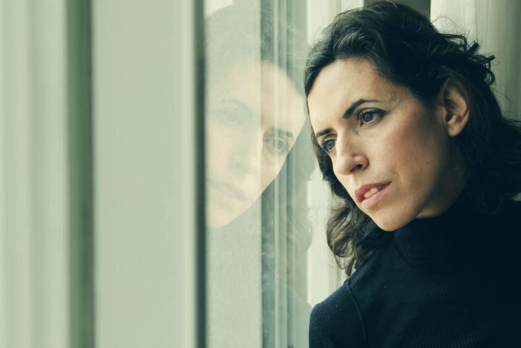 Mulher branca, com expressão apática, sentada no transporte público, apoiando sua cabeça no vidro da janela.