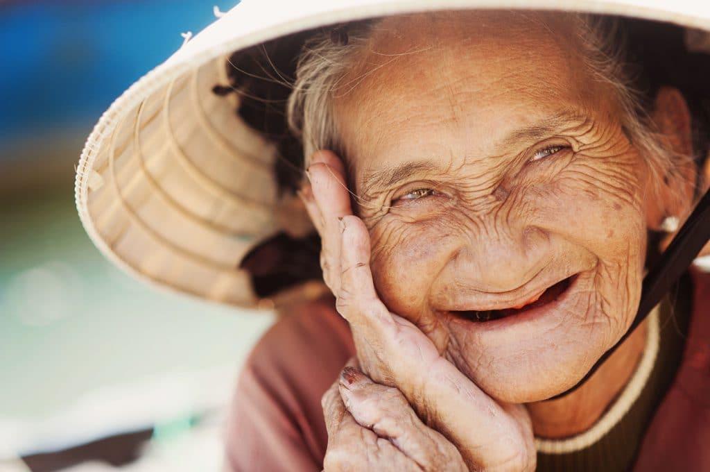 Senhora de idade sorridente, com o rosto cheio de rugas e marcas de expressão.
