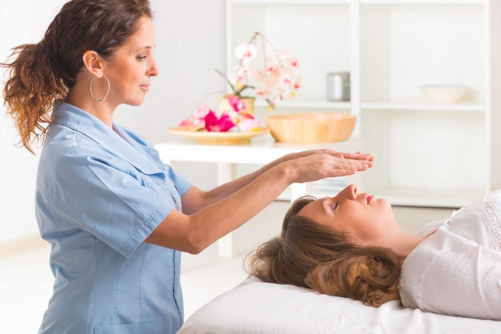 Profissional usando a técnica de Reiki para tratar jovem mulher. Angulo lateral para a curandeira.