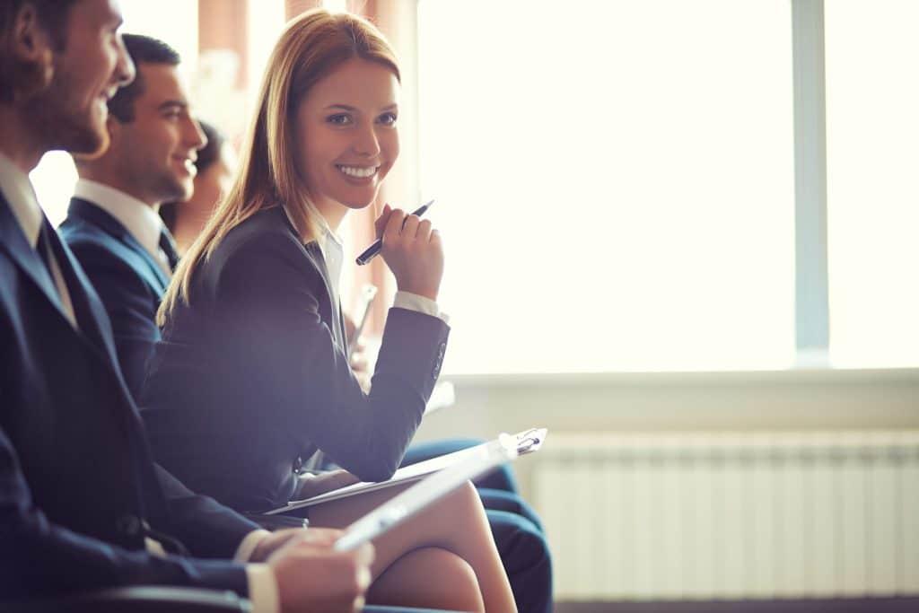Fileira de jovens empreendedores e profissionais. Foco em uma mulher sorrindo.